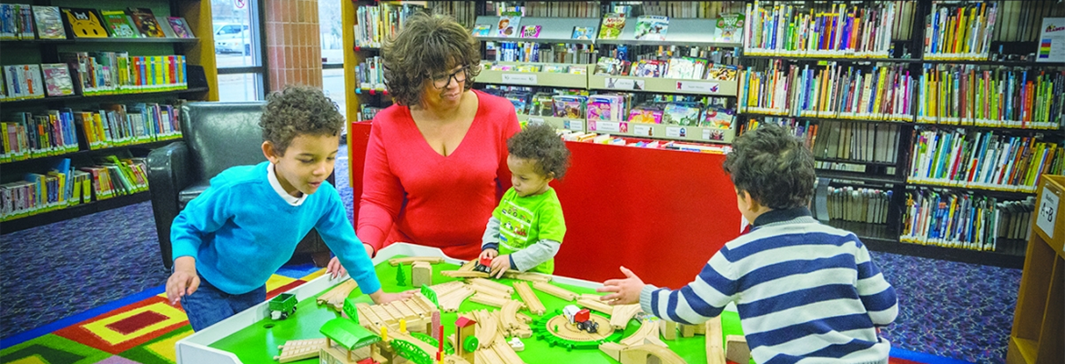 Woman sitting with three young children in the children's area of the library