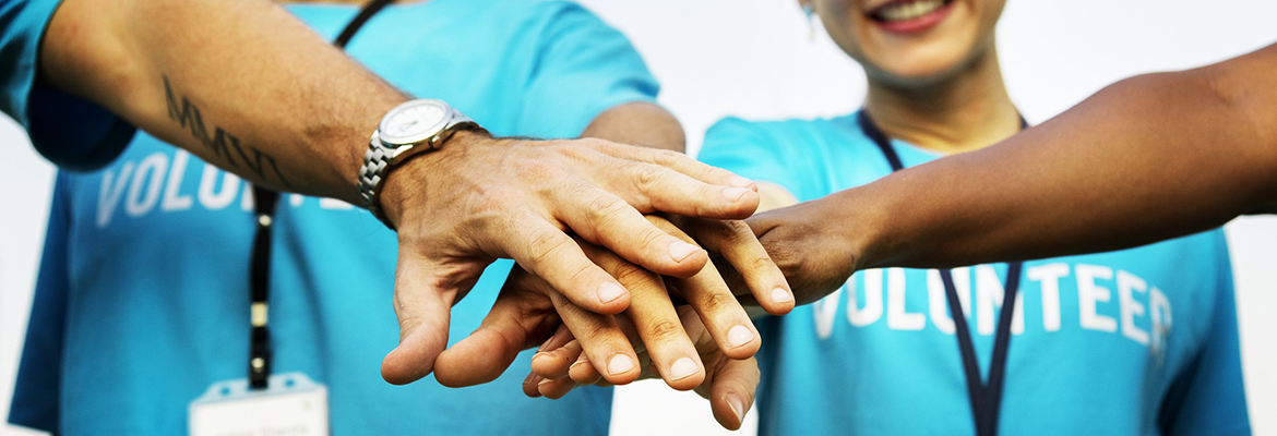 Volunteers stacking their hands after accomplishing something