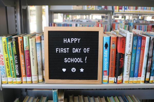 "Photo of letterboard with ""Happy First Day of School!"" sitting on library book shelf."