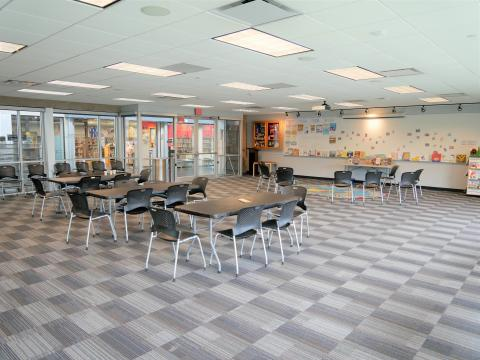 East Side Meeting Room with rectangular tables, chairs, large whiteboard, and chairs lined up against glass wall