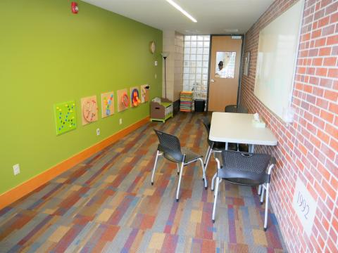 Forest Avenue Study Room with lime green wall, brick wall, and a rectangular table with chairs and a mounted whiteboard